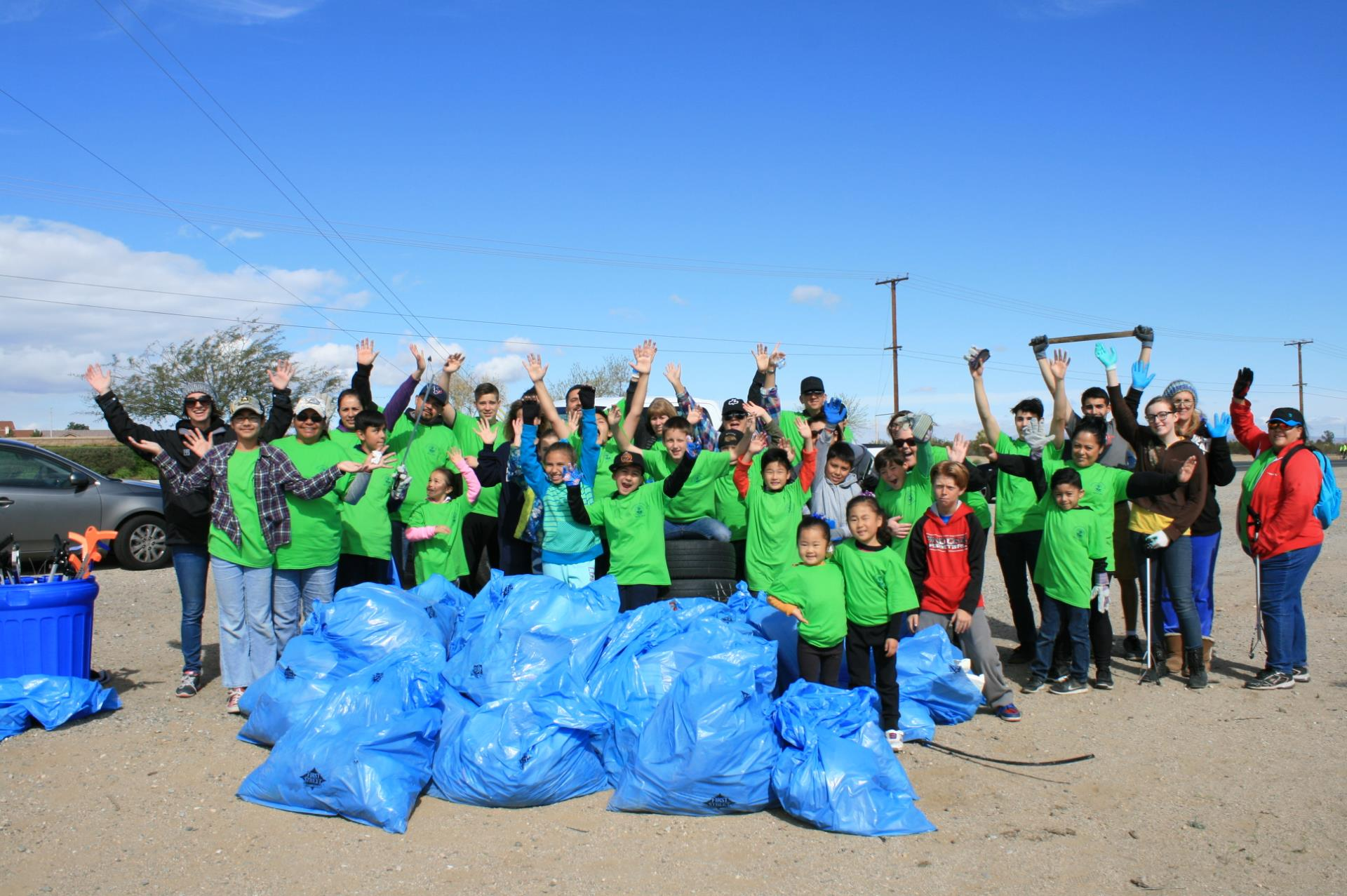 Community Clean Up big group with bags hands in air little volunteers